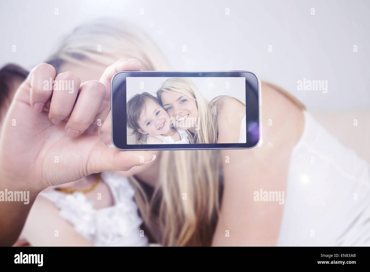 Composite image of hand holding smartphone showing - Stock Image