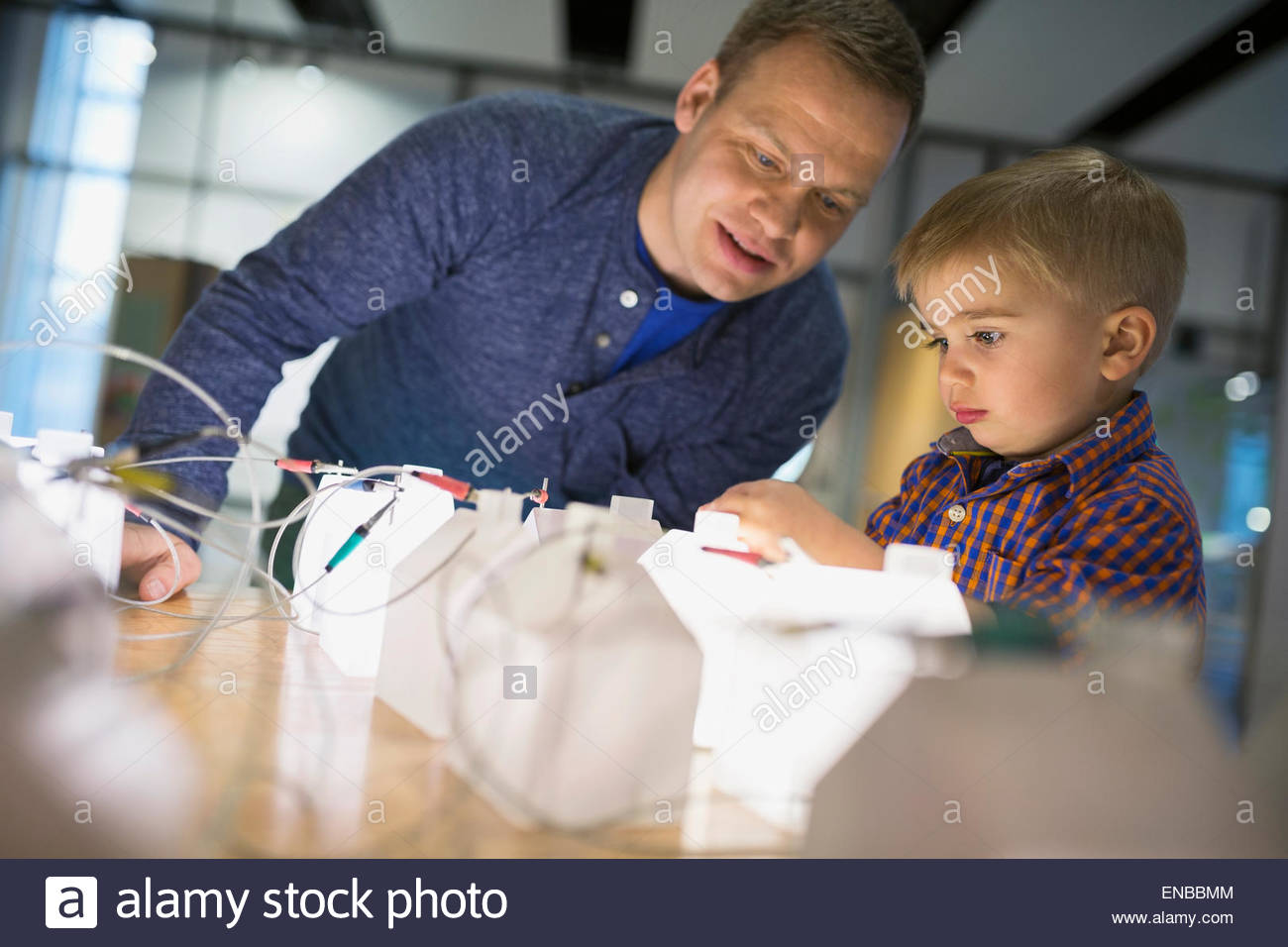 Father and son playing electricity grid science center - Stock Image