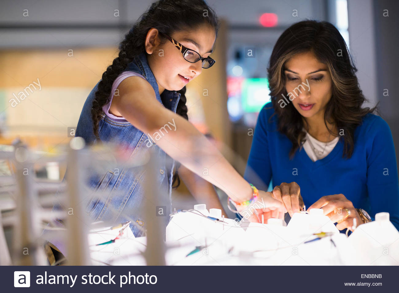 Mother daughter playing electricity exhibit at science center - Stock Image