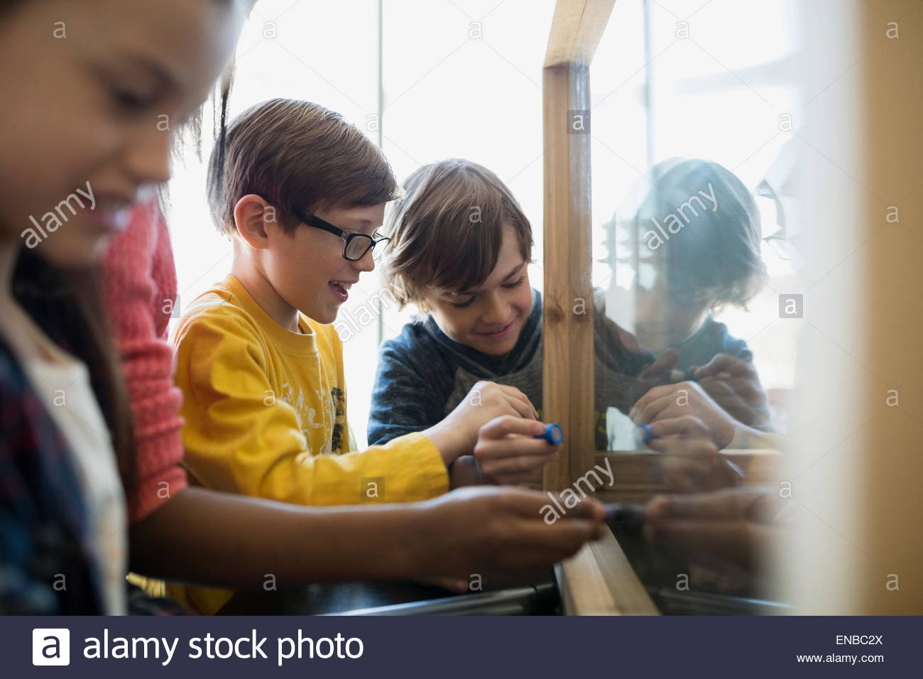 Students at glass board in science center - Stock Image
