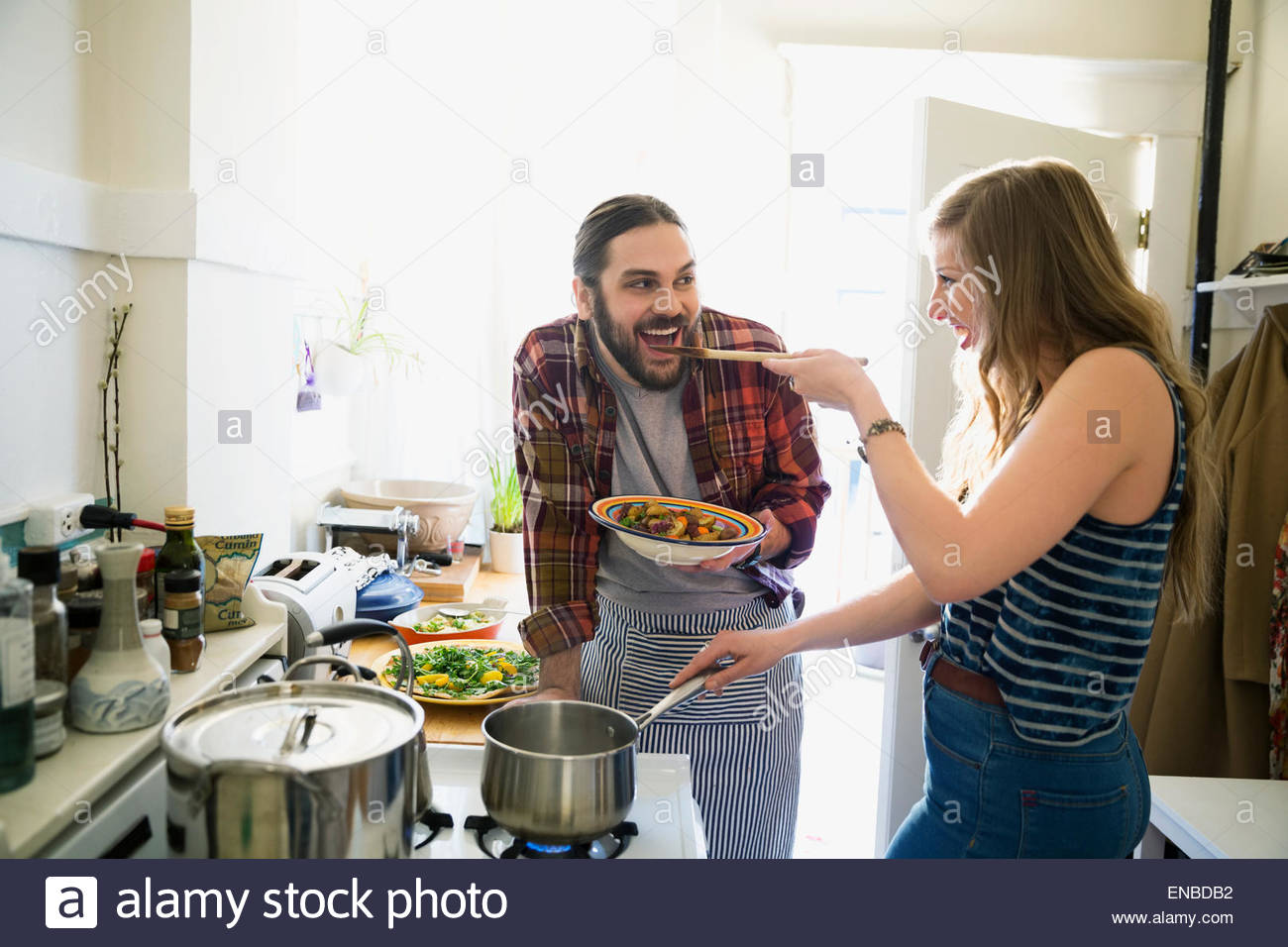 Couple cooking and tasting in kitchen - Stock Image