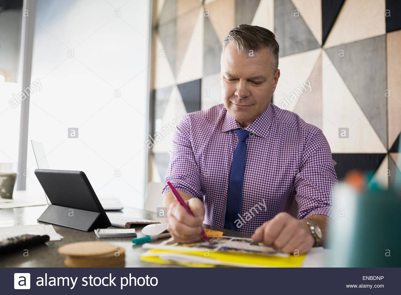 Graphic designer editing proofs in office - Stock Image