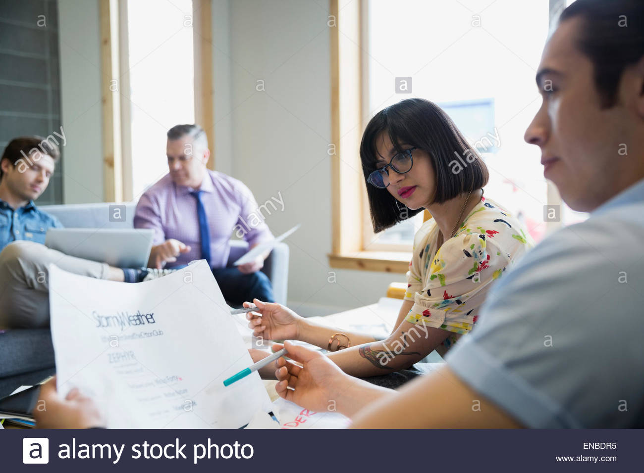 Business people reviewing paperwork, in meeting - Stock Image