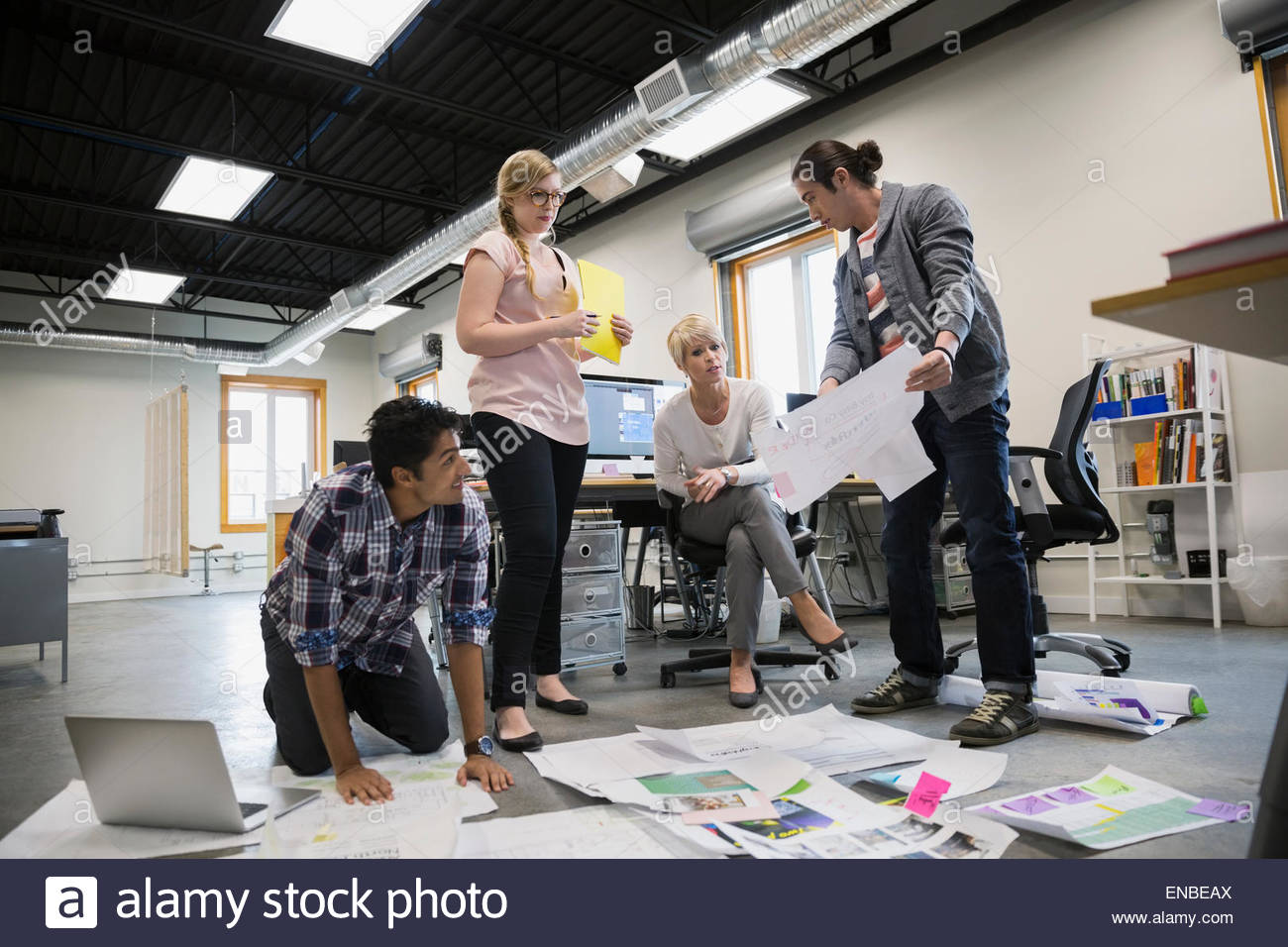 Graphic designers meeting reviewing proofs on office floor - Stock Image