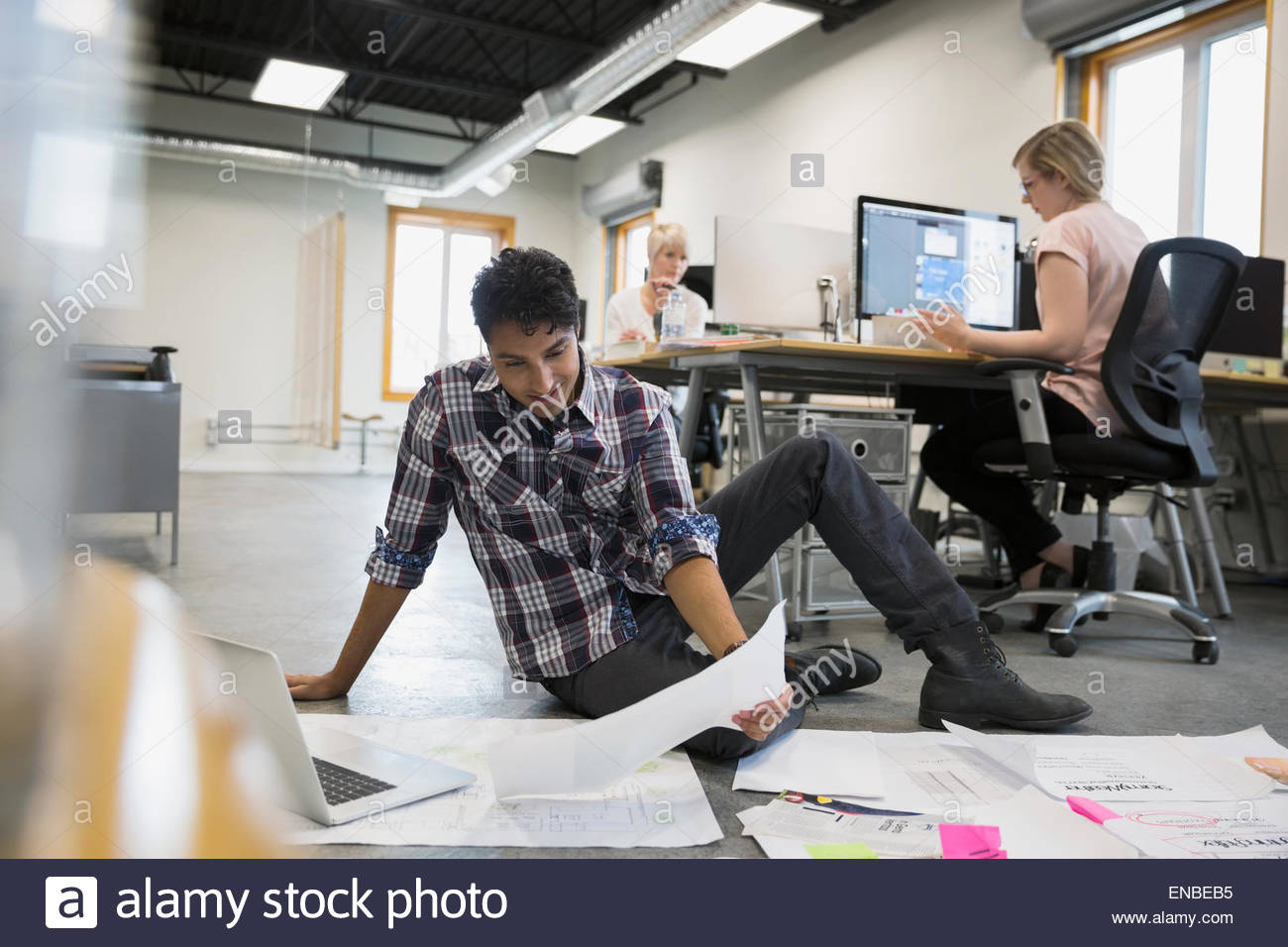 Graphic designer reviewing proofs on office floor - Stock Image