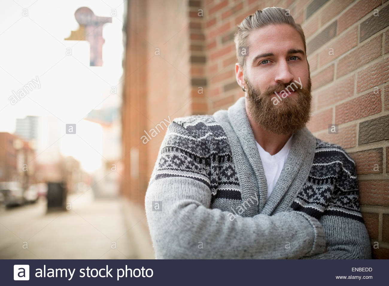 Portrait confident bearded man sweater leaning brick wall - Stock Image