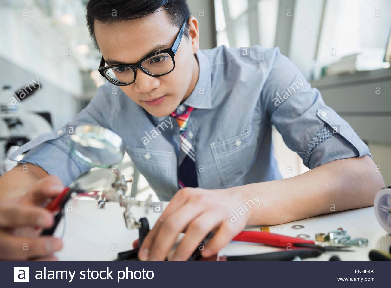 Engineer examining and assembling technology - Stock Image