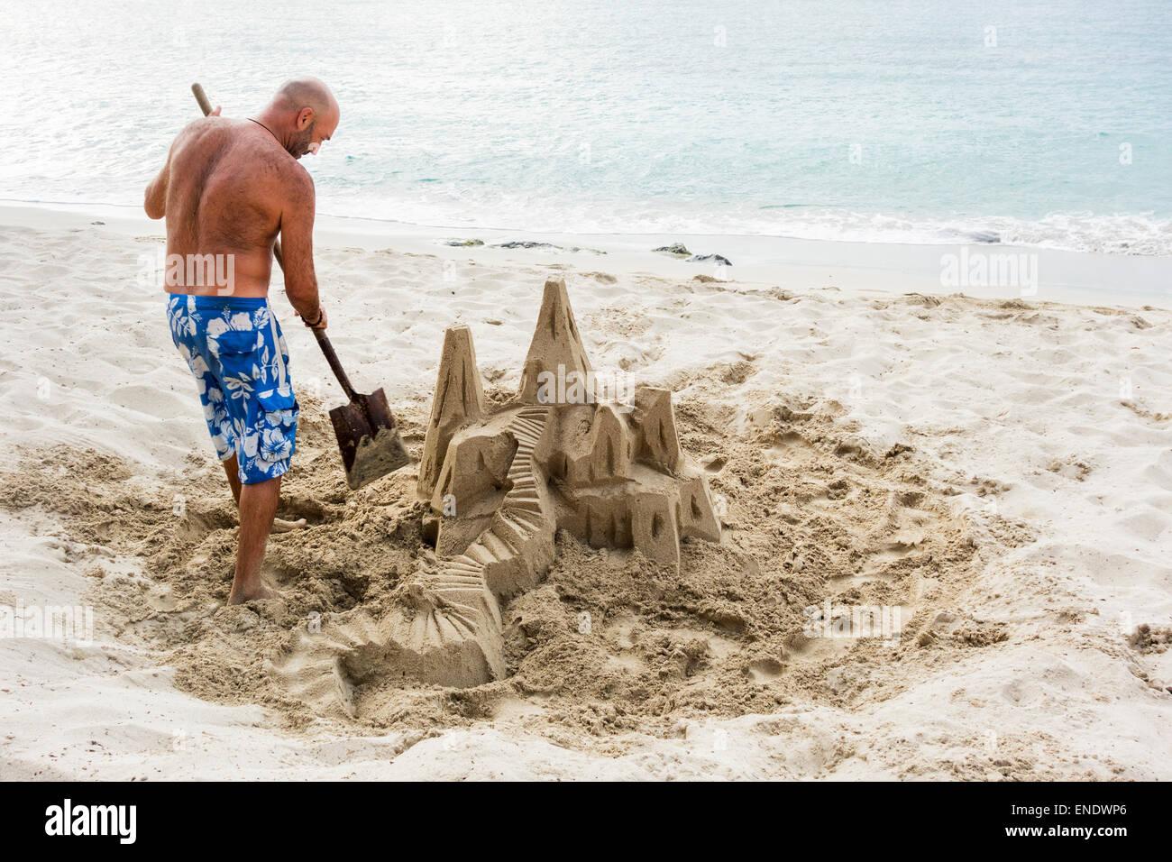 a-caucasian-man-builds-a-sand-castle-on-