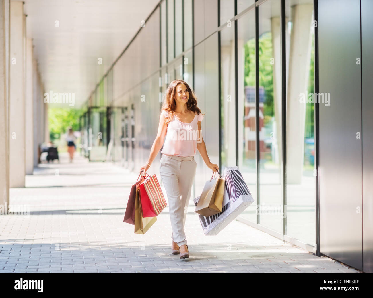 A brown-haired woman wearing muted, gentle colours holds five colourful, patterned shopping bags walks towards the - Stock Image