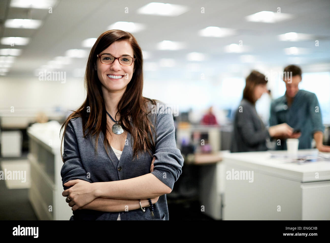 A woman with arms folded smiling. - Stock Image