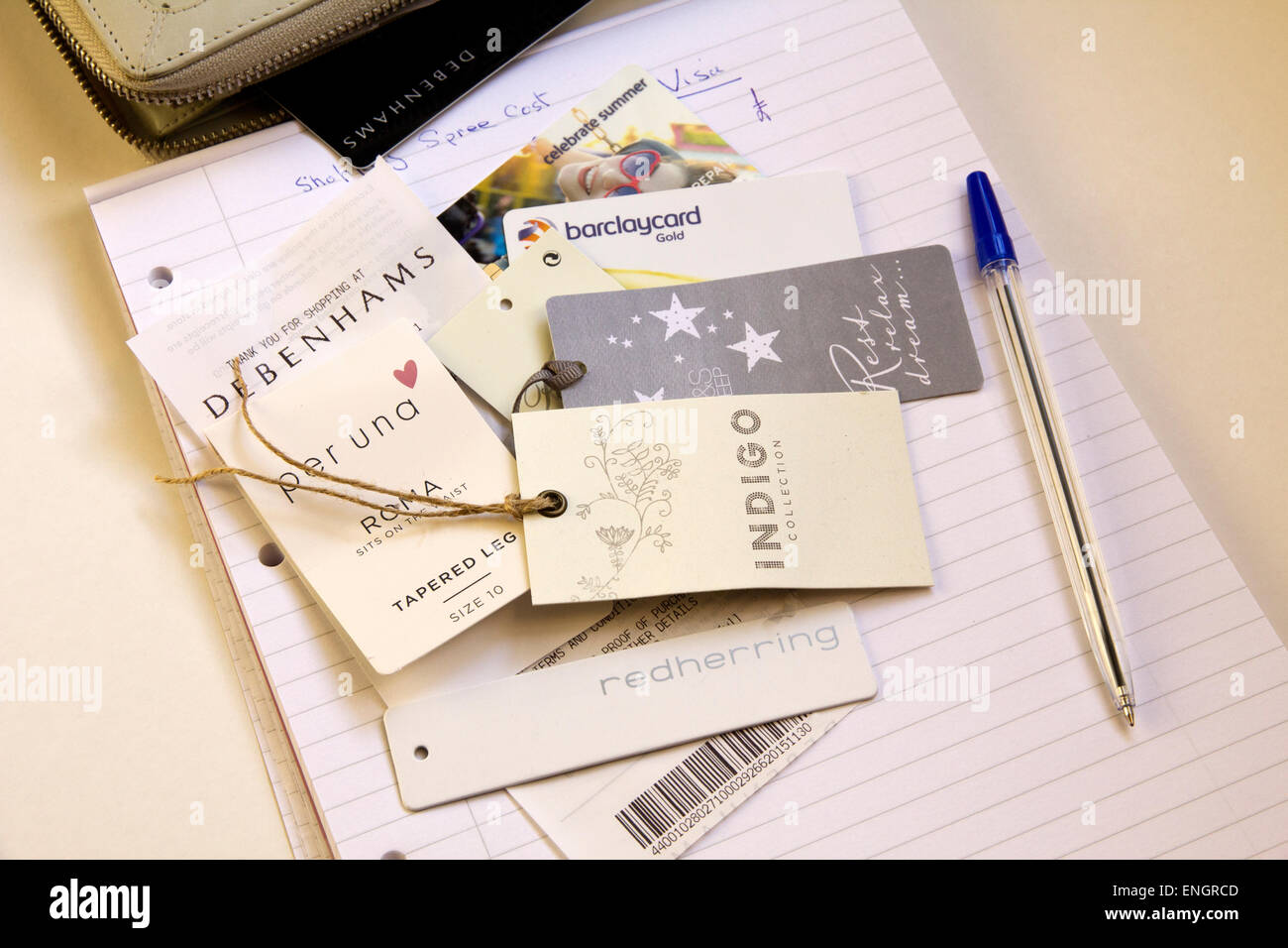 Price Tags, clothing tags, spending cost on note pad, pen. - Stock Image