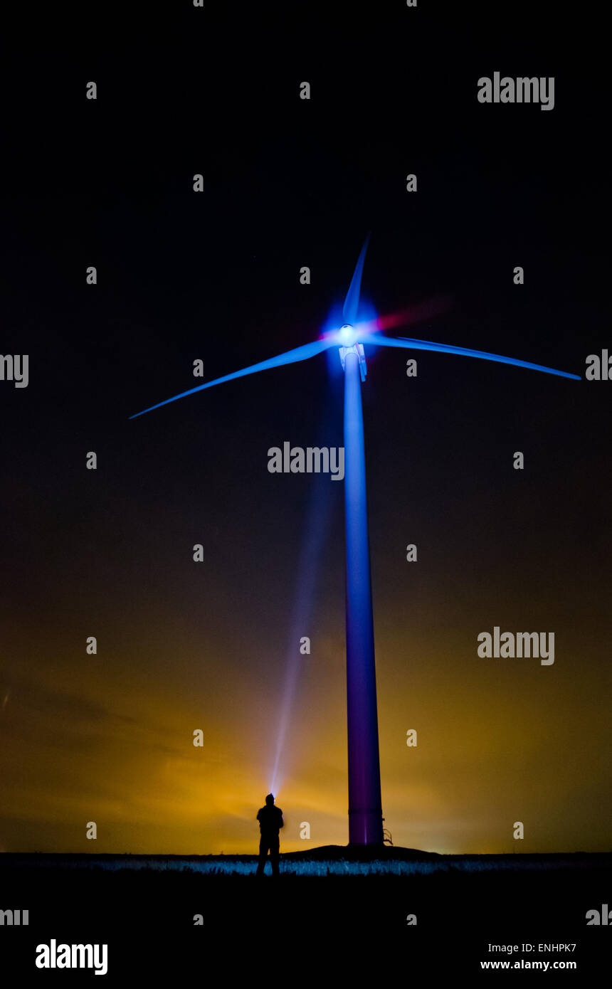 The wind turbine at night in an unusual light- a lonely man shines screw with flashlight . The concept of eco-friendly - Stock Image