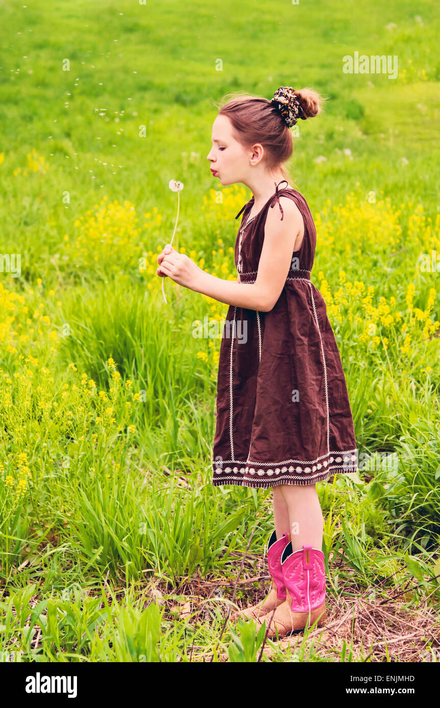 Girl in country meadow blows on dandelion - Stock Image