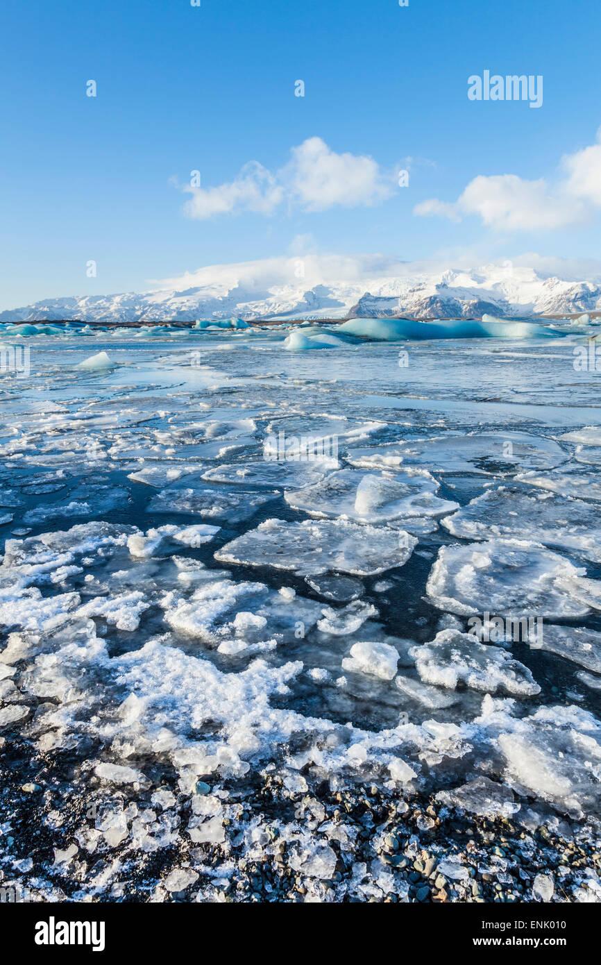 Mountains behind the frozen water of Jokulsarlon Iceberg Lagoon, Jokulsarlon, south east Iceland, Polar Regions - Stock Image