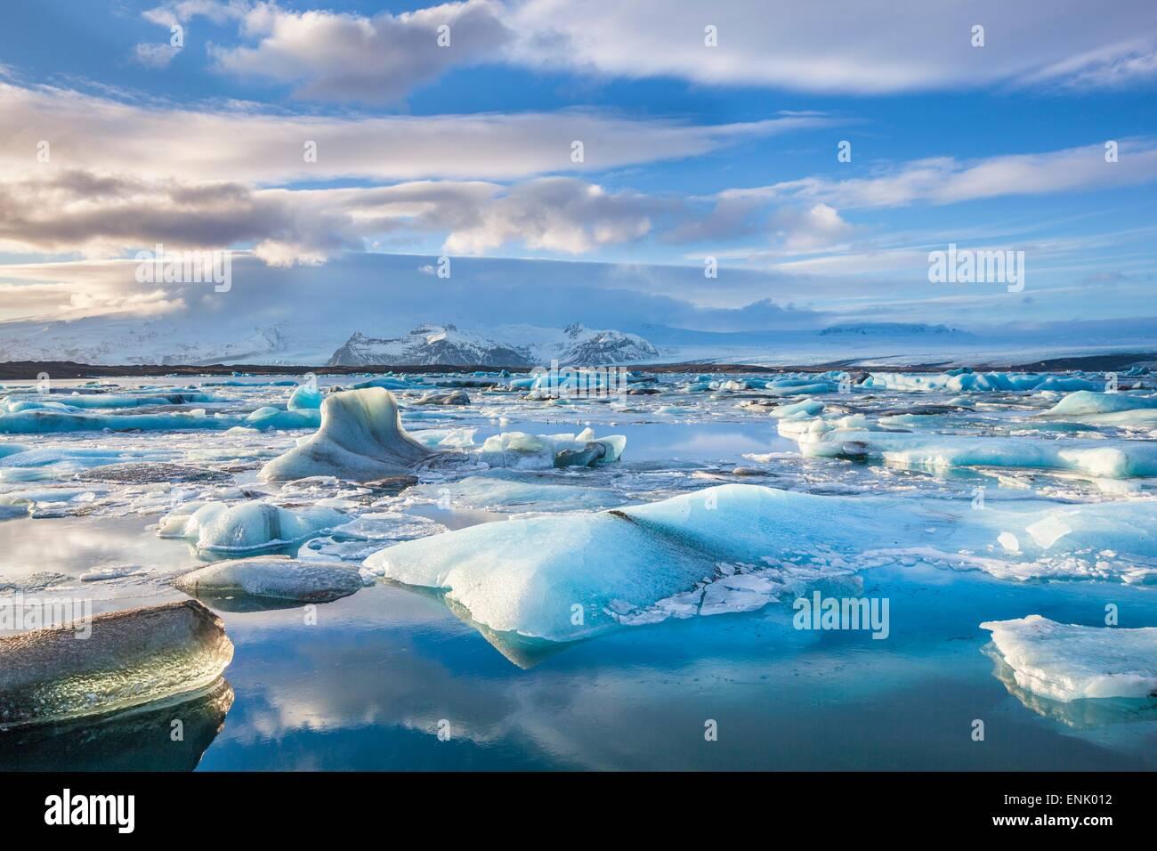 Mountains behind icebergs locked in the frozen water of Jokulsarlon Lagoon, Jokulsarlon, southeast Iceland, Iceland - Stock Image