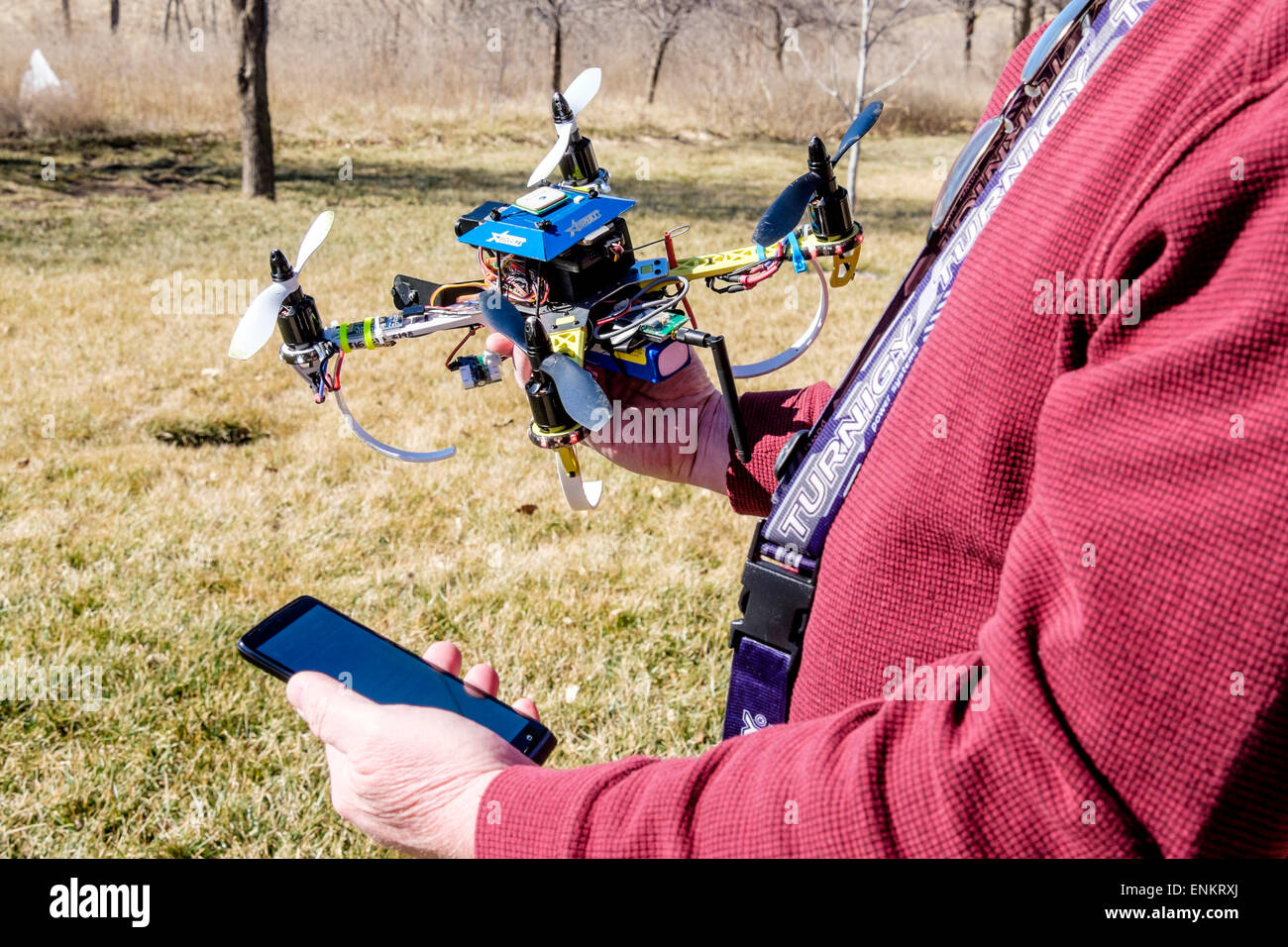 A 50 year old caucasian man holds his do it yourself built a 50 year old caucasian man holds his do it yourself built quadcopter dronewhile looking at his mobile phone outdoors usa solutioingenieria Images