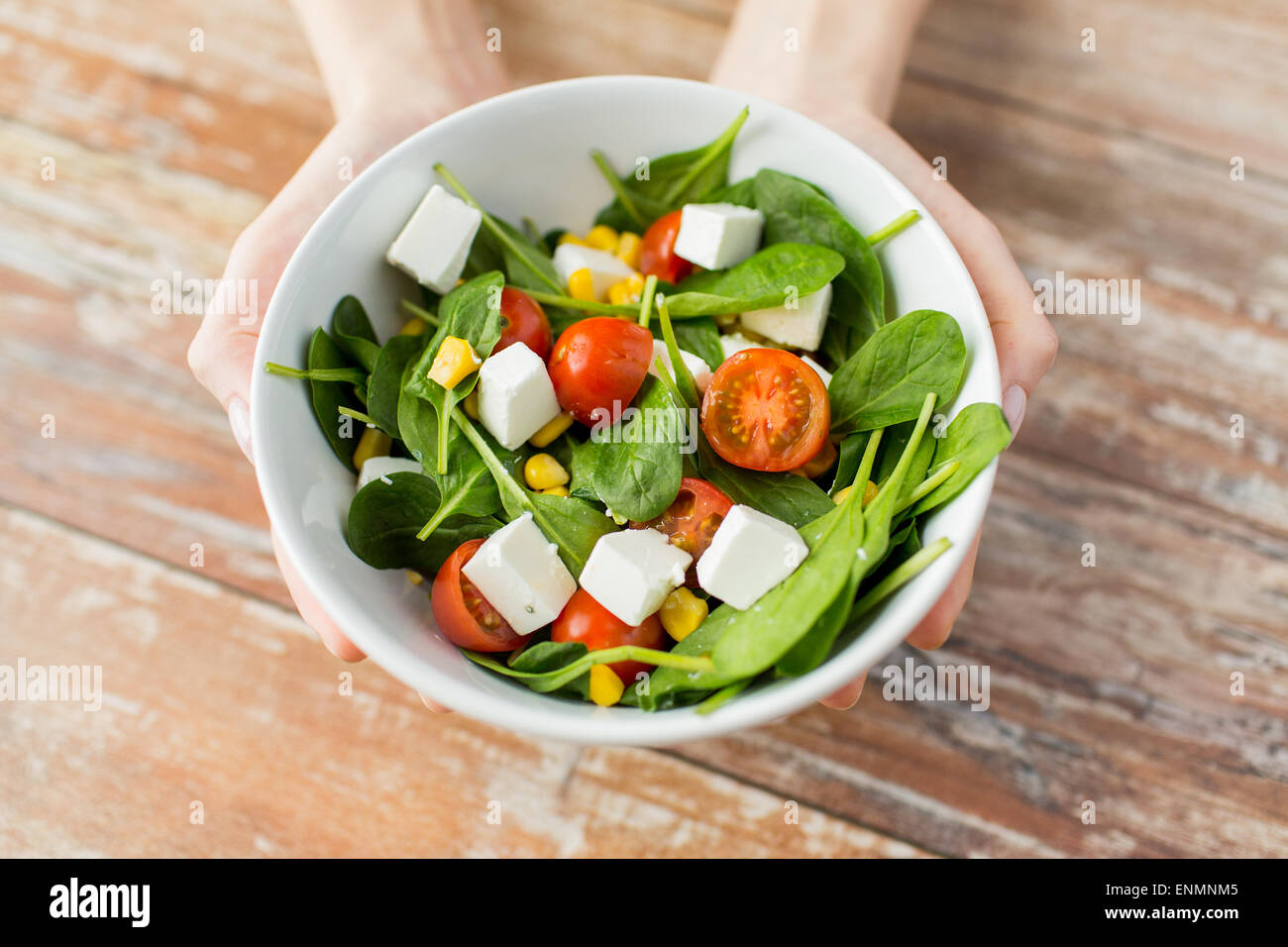 close up of young woman hands showing salad bowl - Stock Image