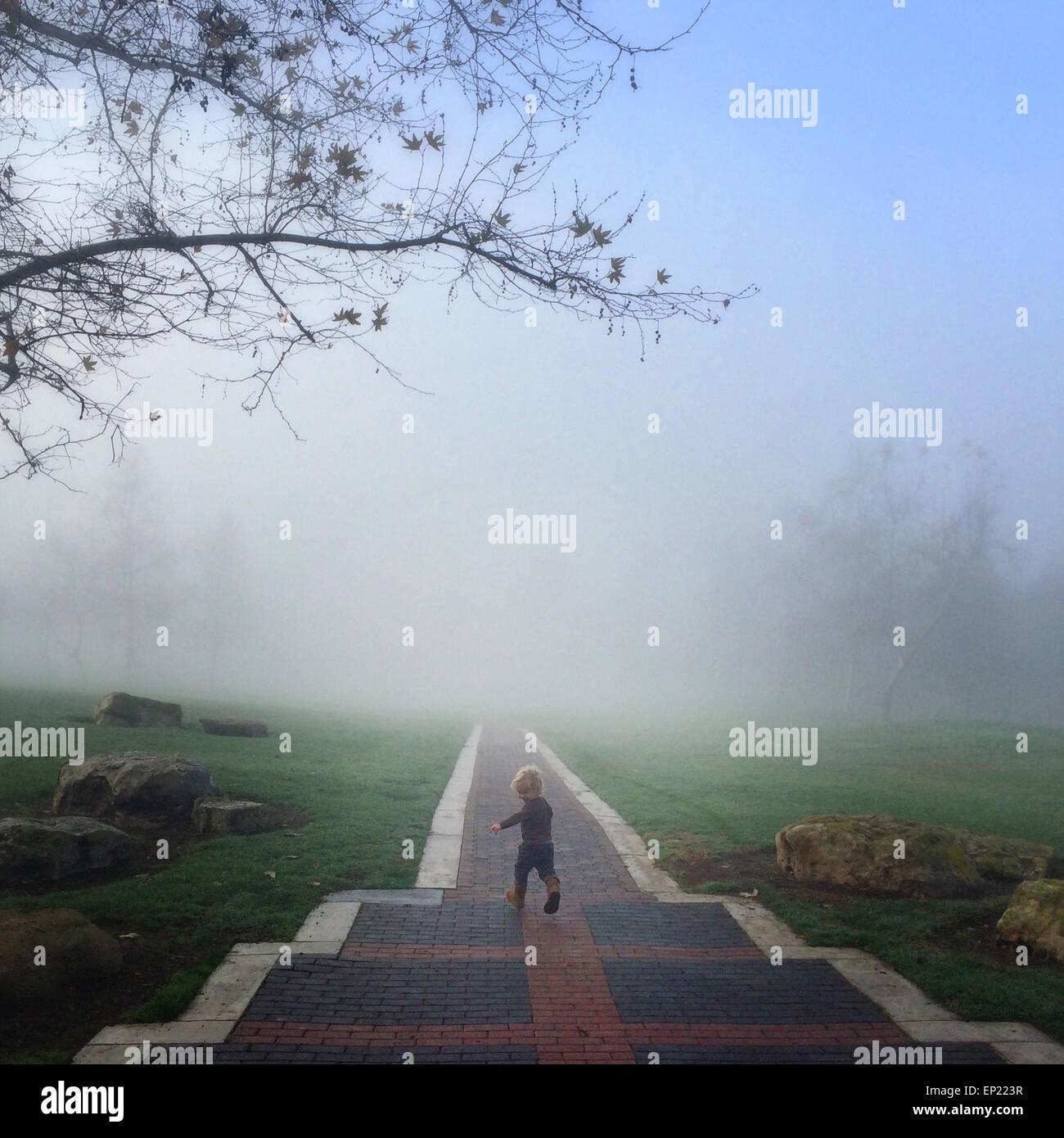 Boy running down path laughing - Stock Image