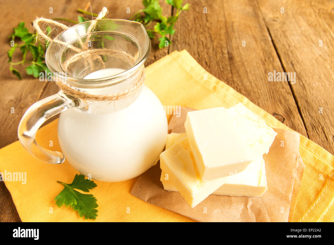 Butter and milk (dairy products) over rustic wooden table - Stock Image