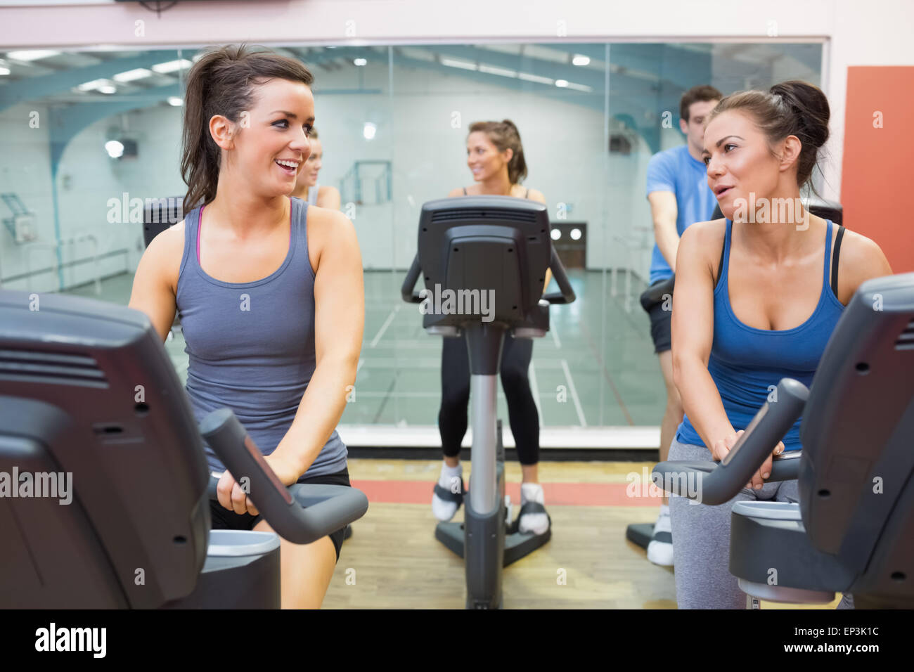 Two women talking  while training in a spinning class - Stock Image