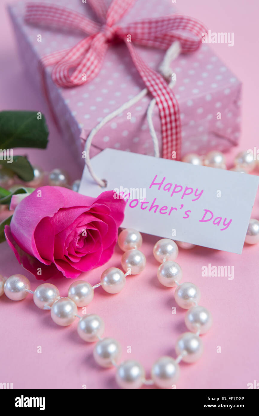 Pink rose with gift and string of pearls for mothers day Stock Photo ...