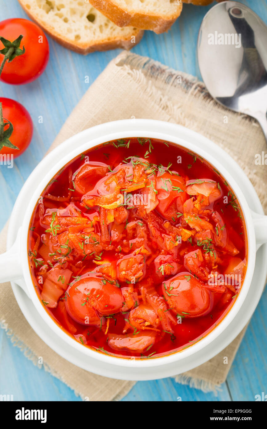 Vegetable soup made of cherry tomatoes, carrot, potato, cabbage in a bowl - Stock Image