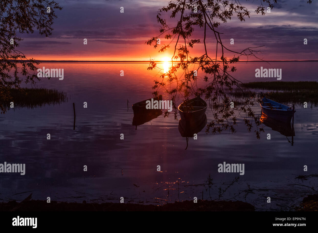 three boats on pier expect the owners from a decline till the dawn - Stock Image
