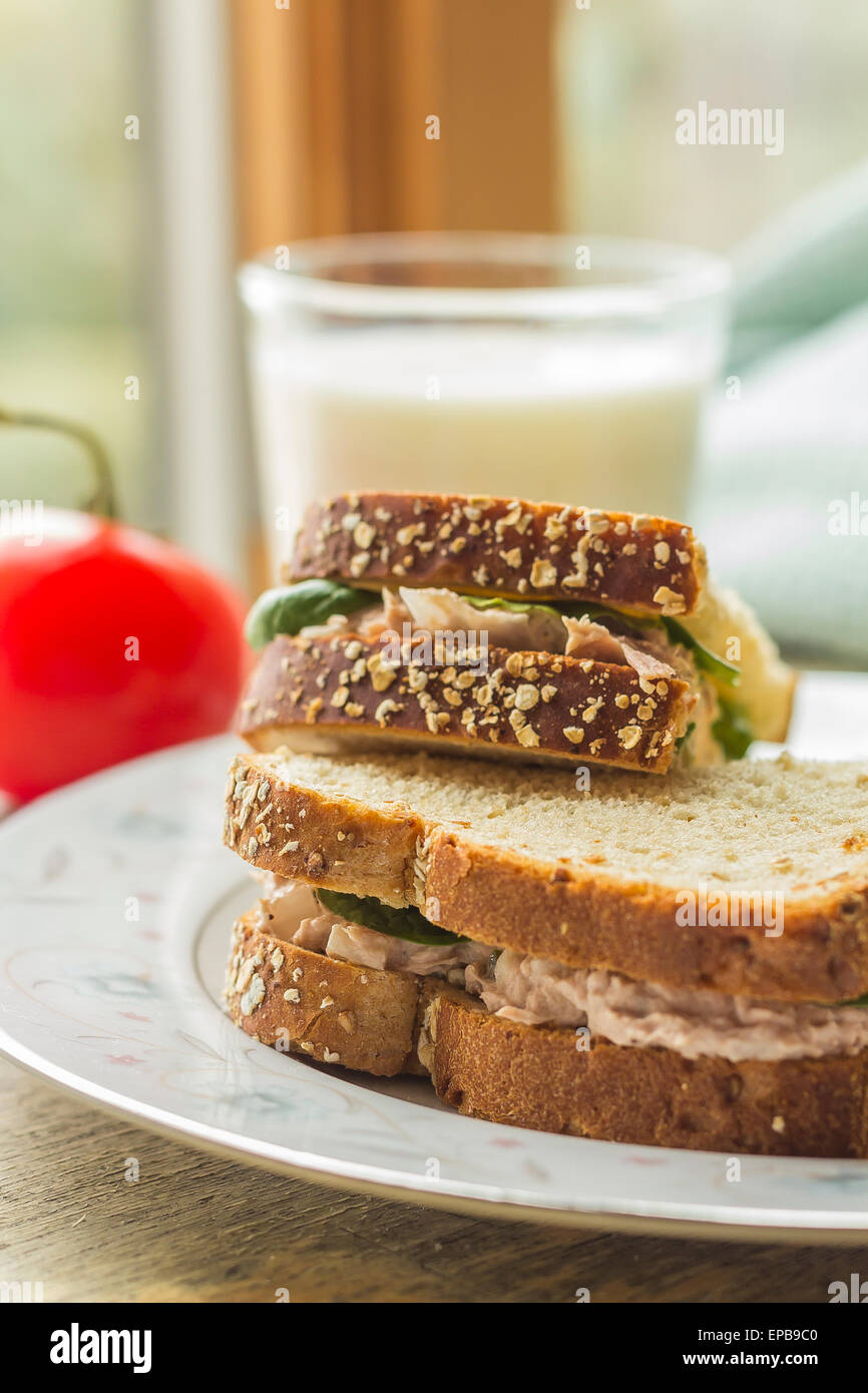 Tuna salad sandwich with ripple potato chips and a glass of milk - Stock Image