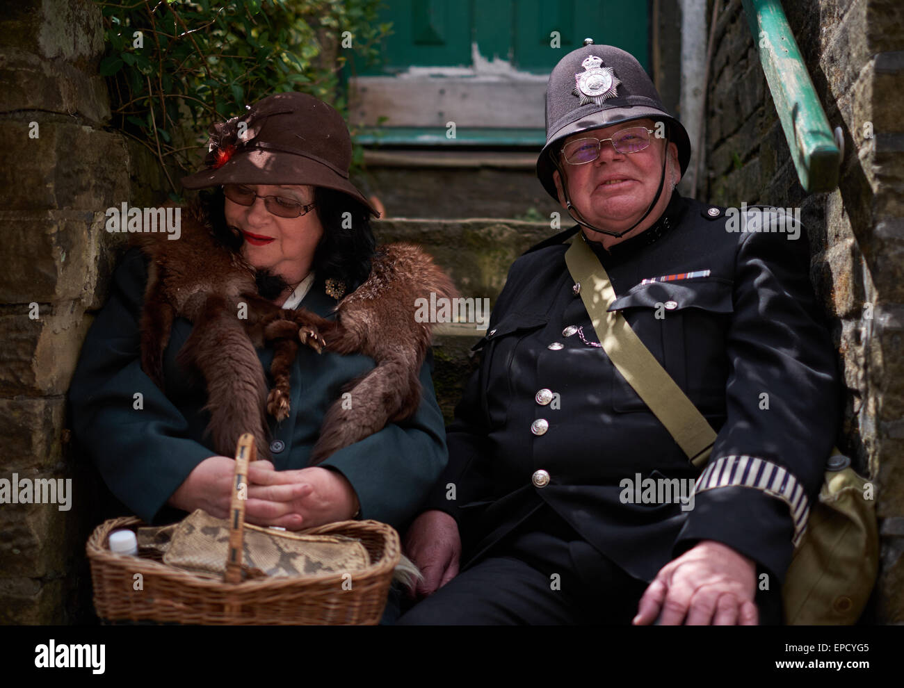 Jolly old policeman and wife sitting in a stairwell - Stock Image
