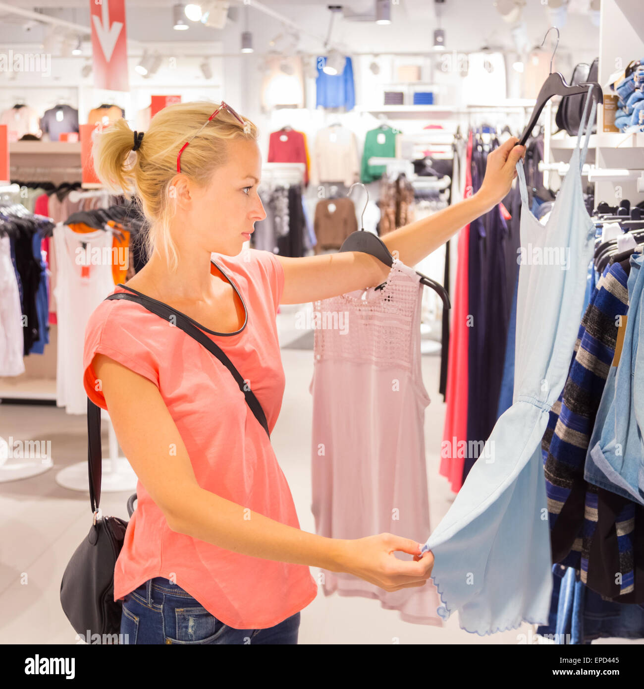 Beautiful woman shopping in clothing store. - Stock Image