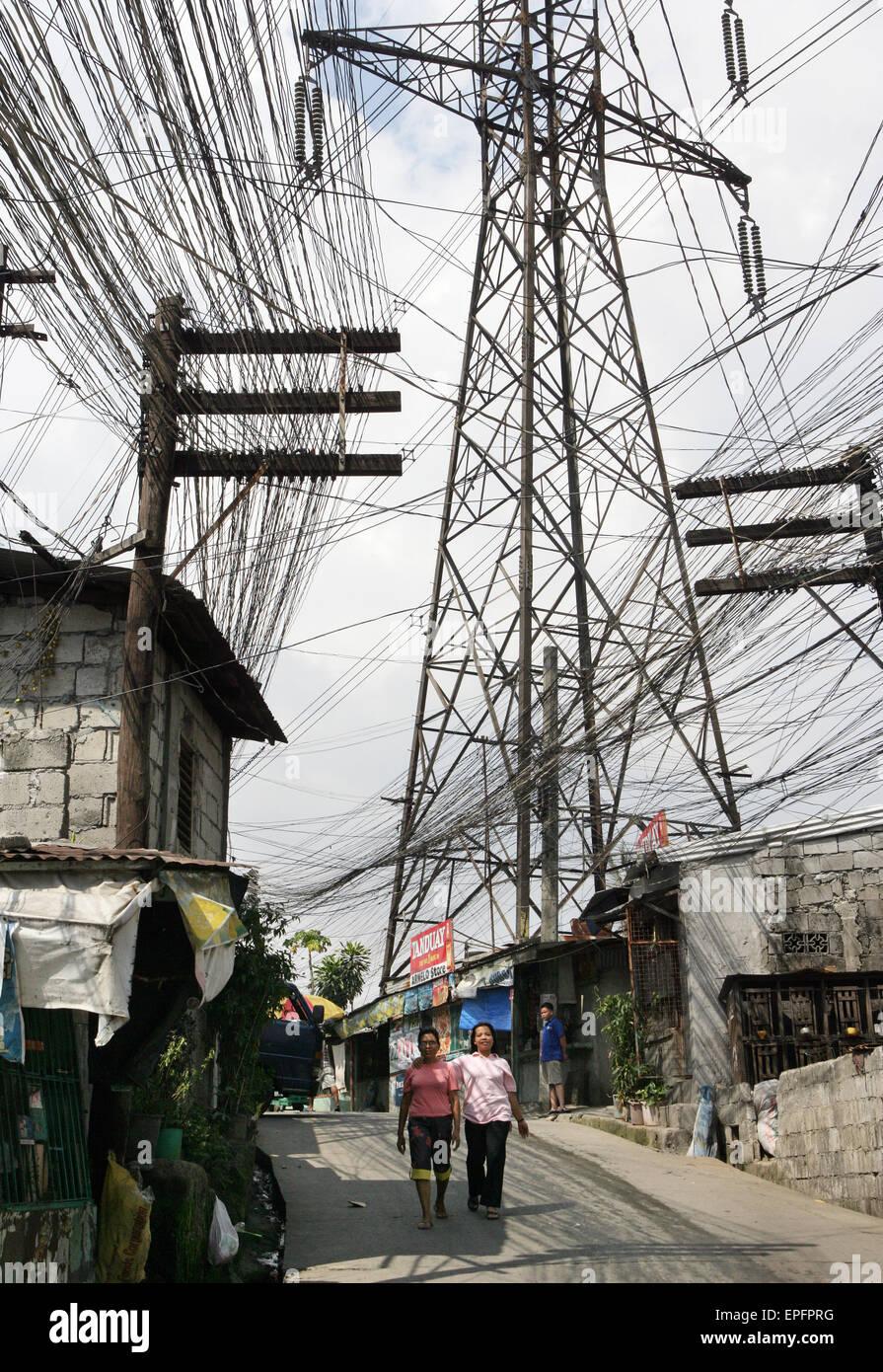 Houses under the electricity pylons in the slum Valenzuela. Manila ...