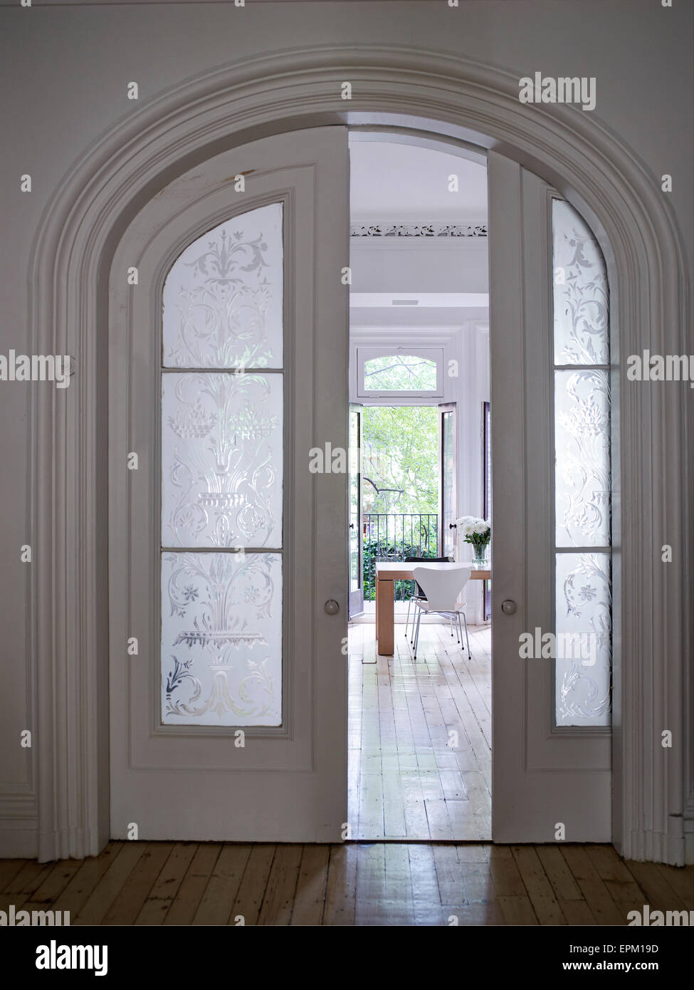 Wood and glass sliding doors in arched doorframe, Chelsea Townhouse, New York, USA - Stock Image