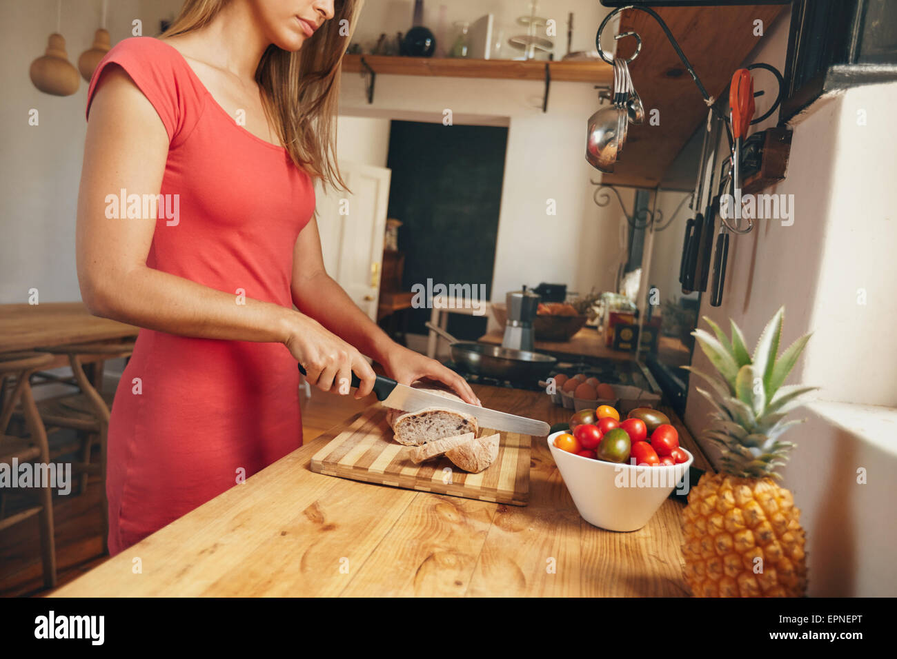 Cropped shot of a young woman slicing a fresh baked loaf of bread on a domestic kitchen counter. Female making morning - Stock Image