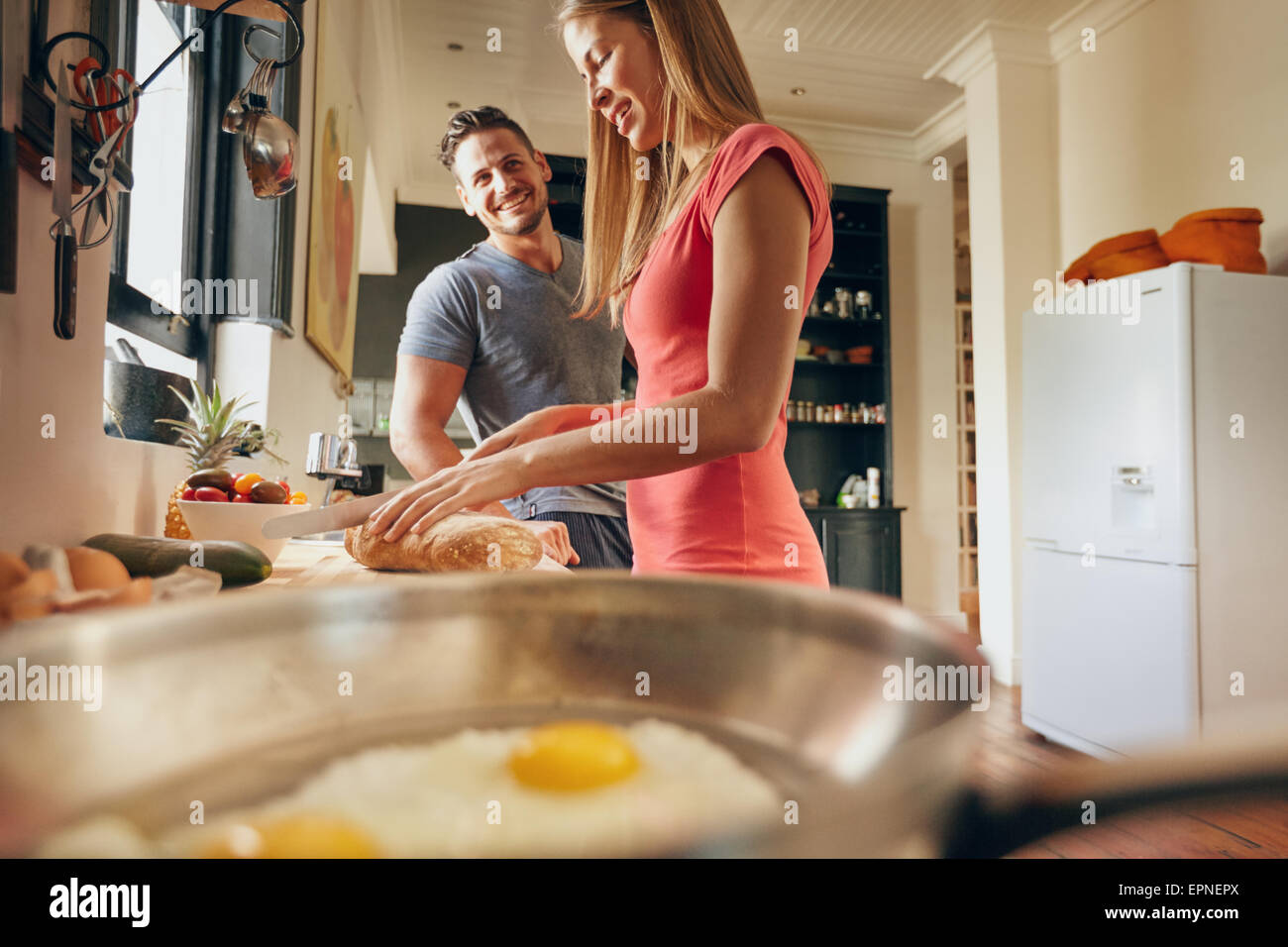 Indoor shot of happy young couple standing at the kitchen counter in morning. Woman cutting bread for breakfast. - Stock Image