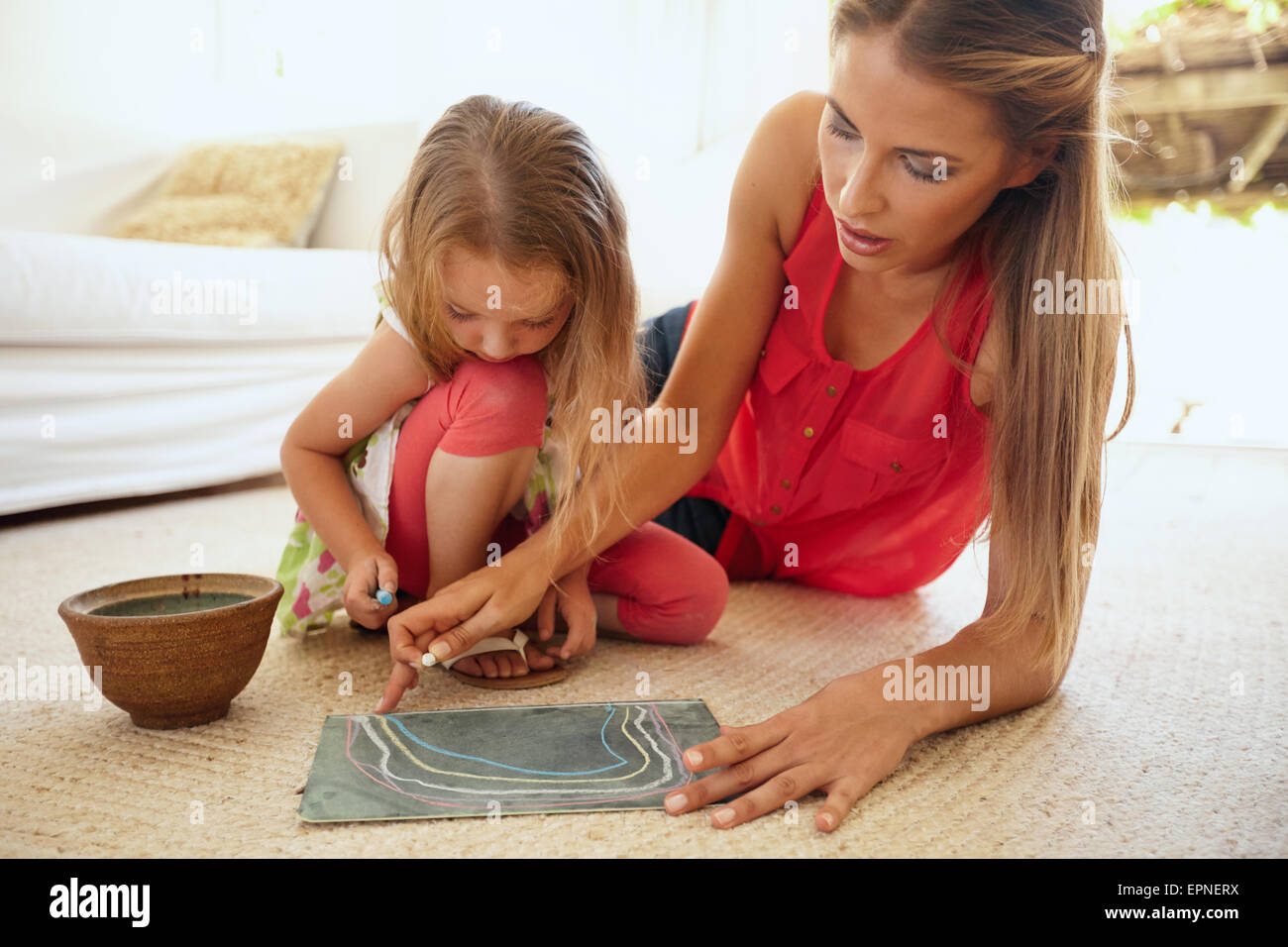 Portrait of mother and little daughter together drawing pictures using color chalks, both sitting on floor in living - Stock Image