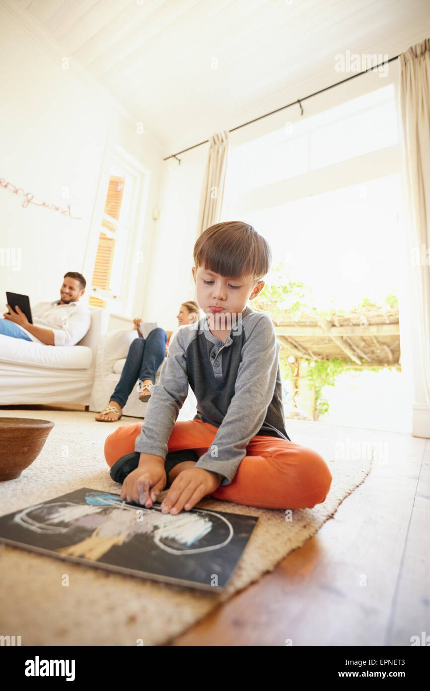 Little schoolboy sitting on floor drawing with his parents sitting in background on couch. Family in living room. - Stock Image