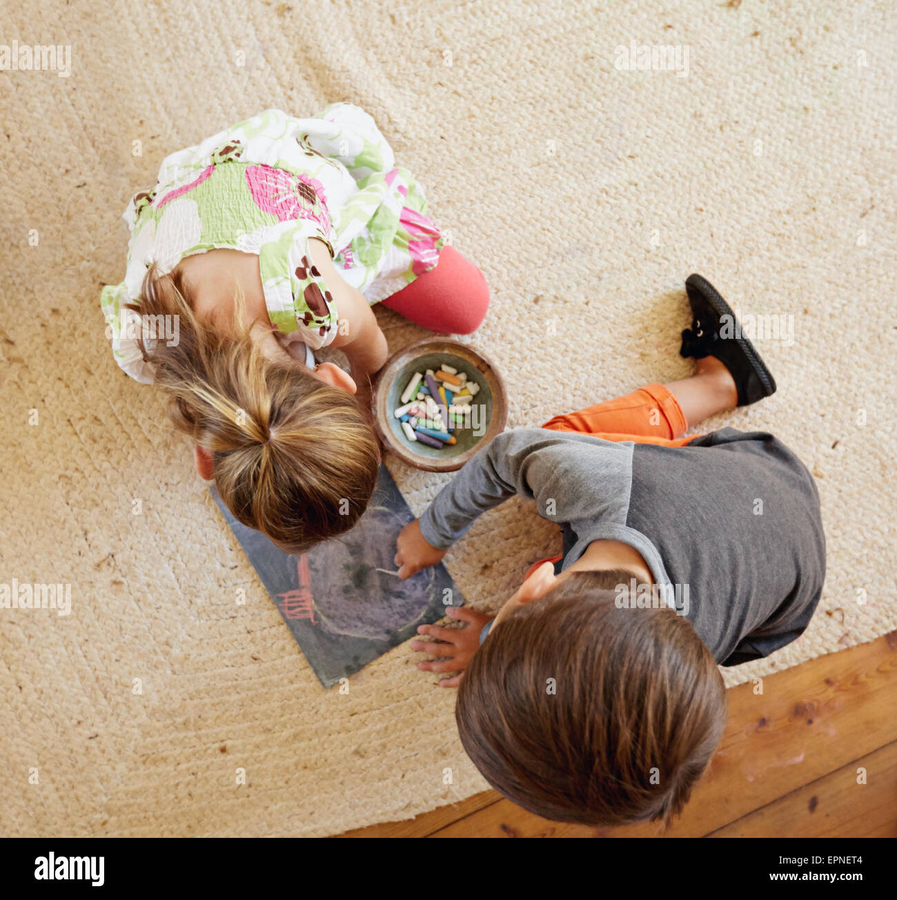 Top view of two little kids sitting on floor drawing with color chalks. - Stock Image