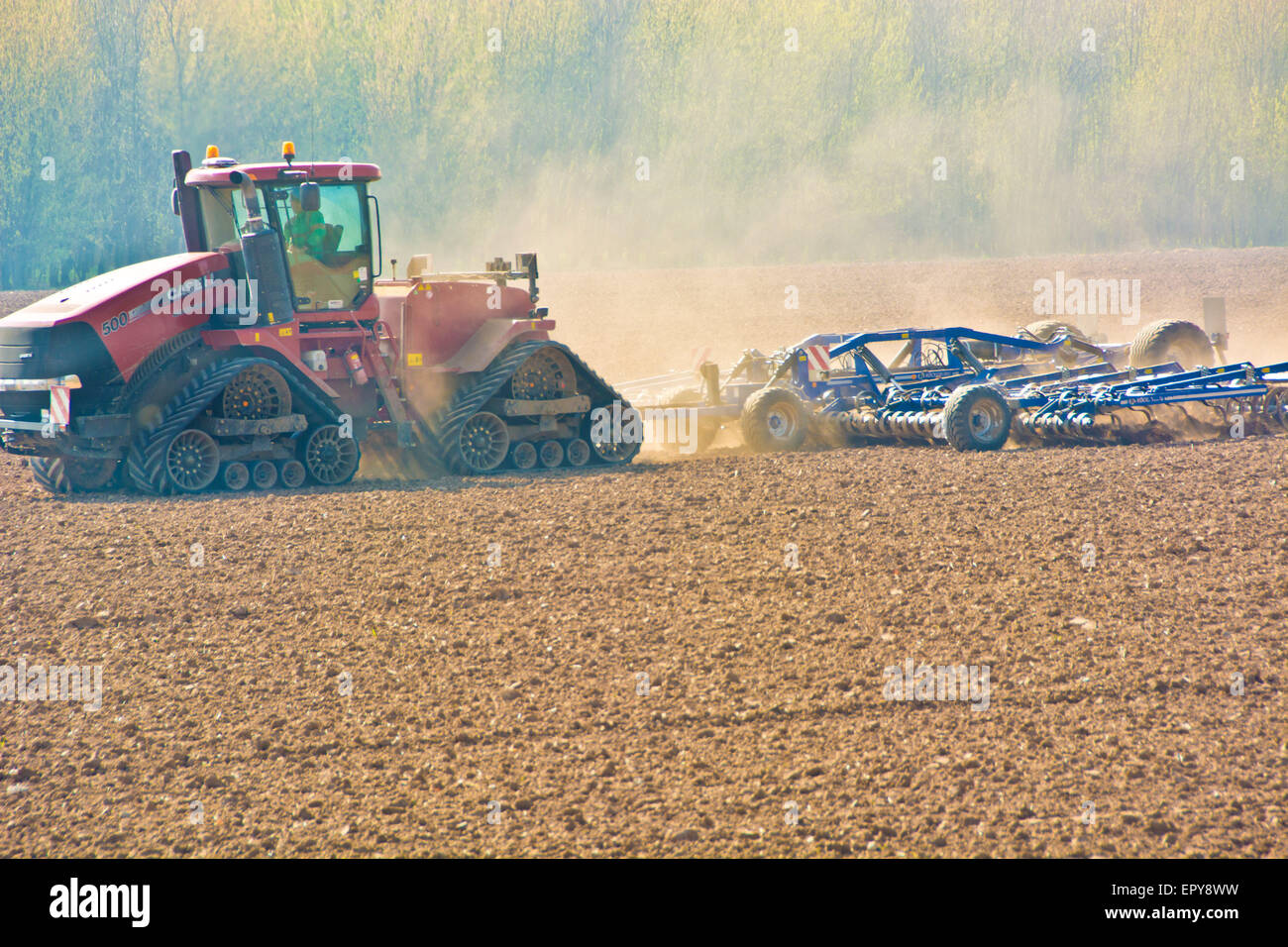 tractor plowing the soil in spring - Stock Image