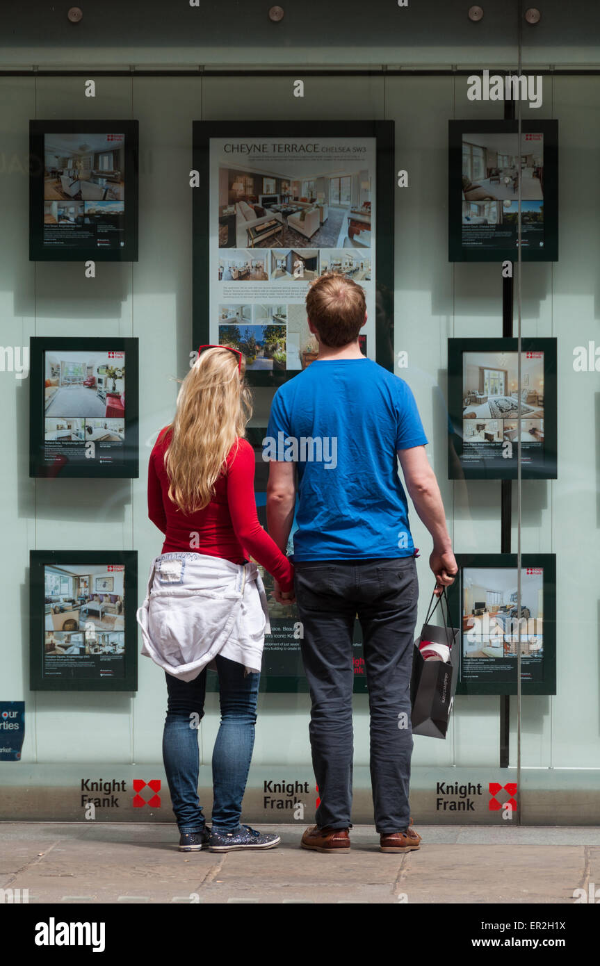 Potential buyer exploring the London property market at Knight Frank shop - Stock Image