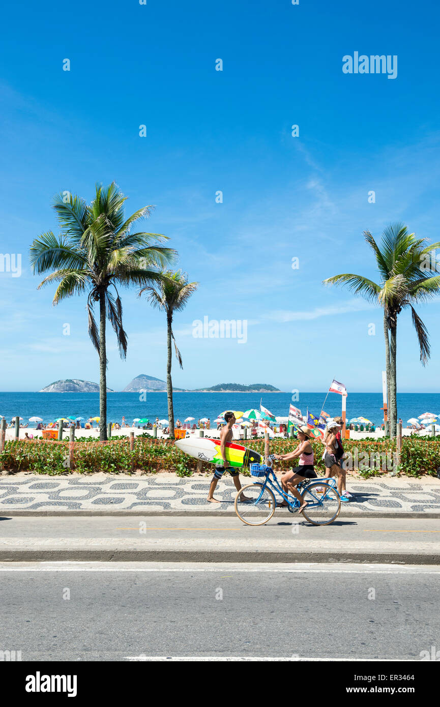 RIO DE JANEIRO, BRAZIL - MARCH 08, 2015: Brazilians walk and ride bicycles with surfboards on the beachfront boardwalk - Stock Image