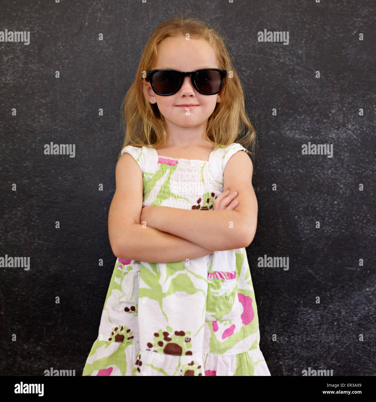 Portrait of cute little girl wearing sunglasses against a black wall. Young girl standing in shades with her hands - Stock Image