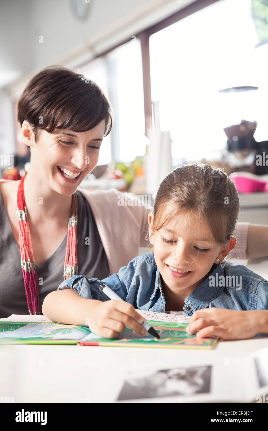 Mother teaching young daughter to read - Stock Image
