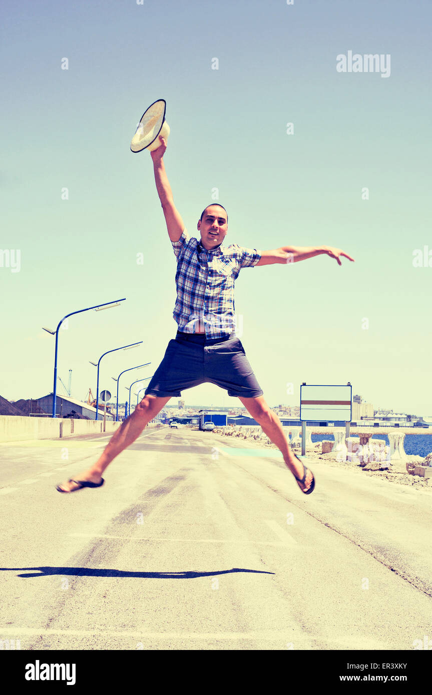 a young caucasian man with a straw hat in his hand jumping in a no traffic road near the sea - Stock Image