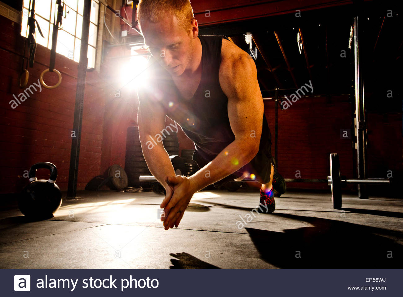 A crossfit athlete works out in a crossfit gym. - Stock Image