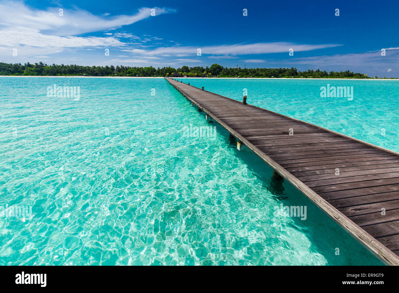 Wooden long jetty over lagoon in Maldives with amazing clean water - Stock Image