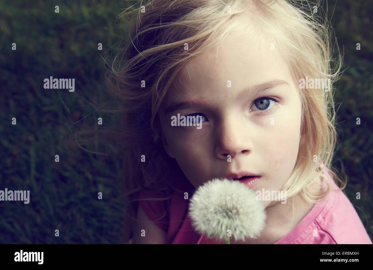 Portrait of caucasian blond girl blowing flower dandelion seeds - Stock Image