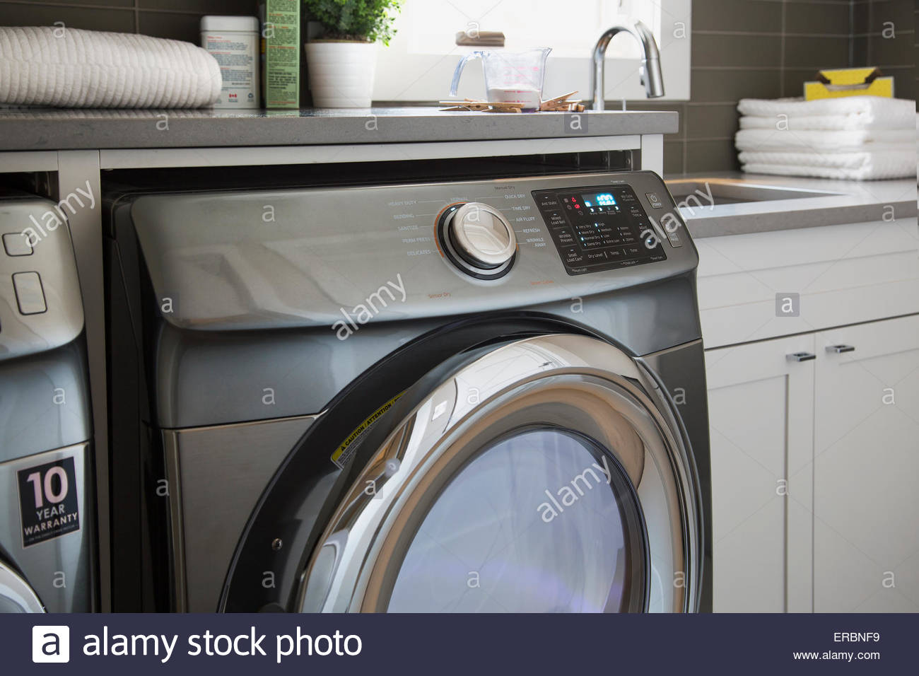 Energy efficient washing machine in laundry room - Stock Image