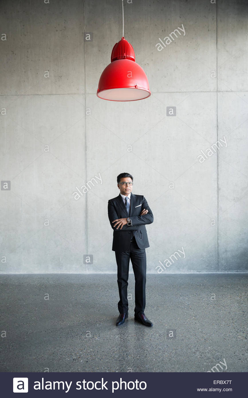 Portrait serious businessman under red lamp - Stock Image