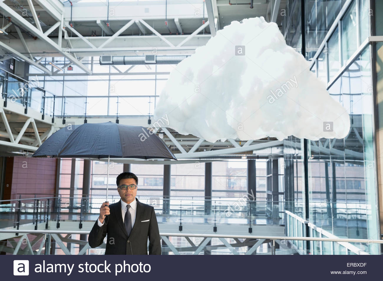 Portrait businessman with umbrella under cloud in atrium - Stock Image