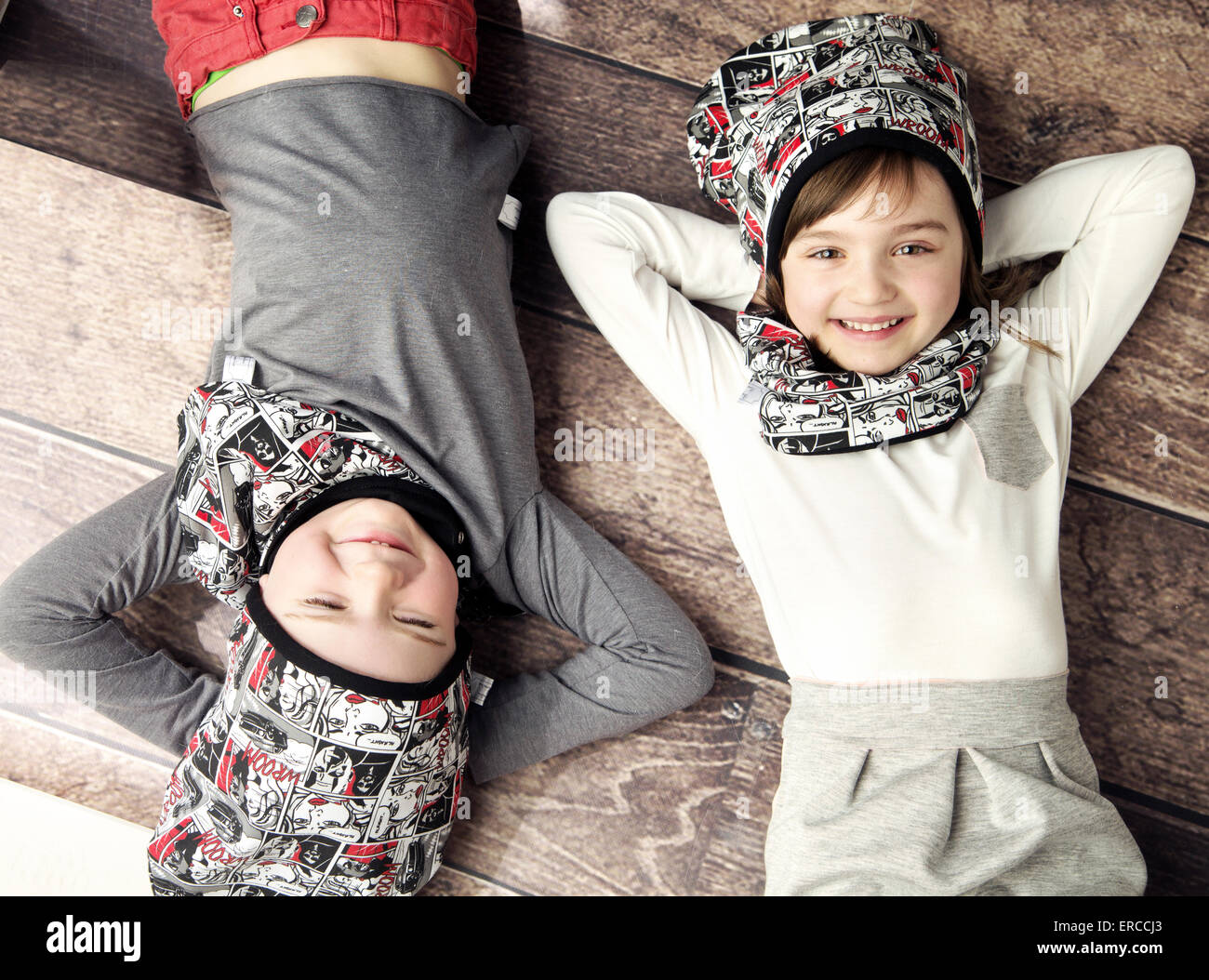 Cheerful kids lying on the wooden floor - Stock Image